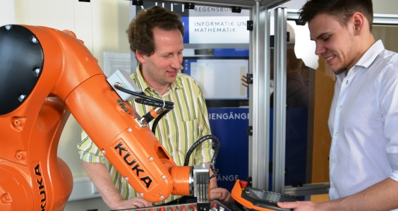 Professor Dr Martin Weiss (left) and Markus Webert working with the Kuka small robot KR Agilus. Source: Kuka Robotics