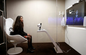 An attendee communicates with Sara, a socially aware robot assistant, during a presentation at WEF. Reuters / Ruben Sprich